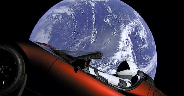 Image: Tesla's red car in outer space, floating past Earth with Rocketman at the wheel