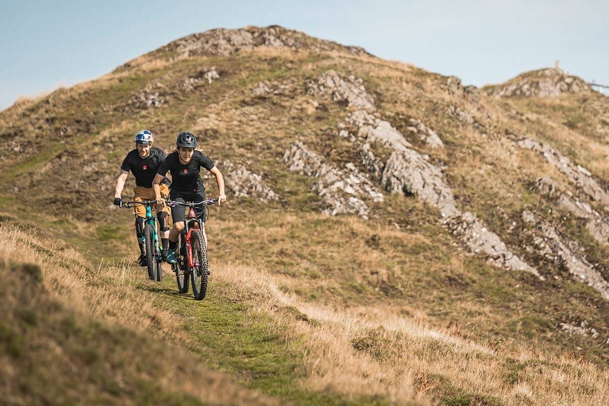 man and woman biking a trail