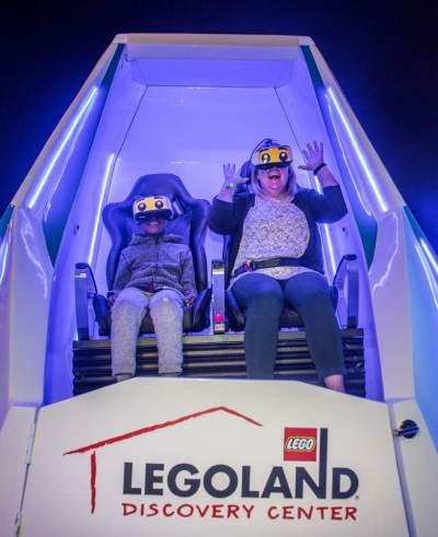 mother and boy enjoy immotion vr experience at legoland discovery center boston