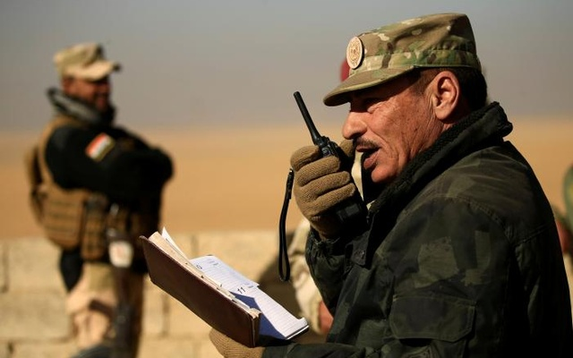 Nineveh Operations Commander Major General Najm al-Jubbouri uses a handheld radio during an operation against Islamic State militants southeast of Mosul, Iraq Nov 26, 2016. Reuters