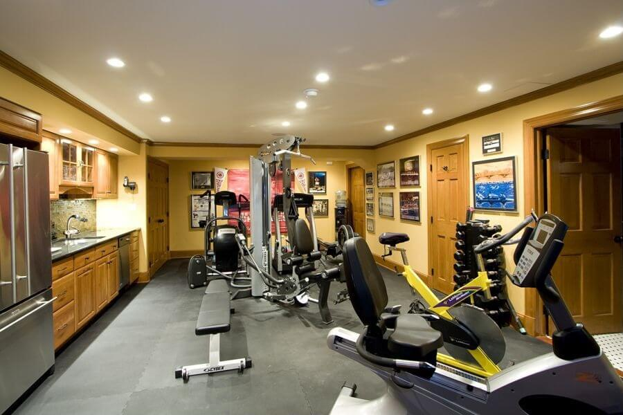 Enclosed home gym in basement of home with cardio equipment and weight machines. Small kitchen in the room as well.