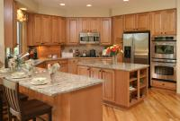 Solidly U-shaped kitchen here awash in warm natural wood ...
