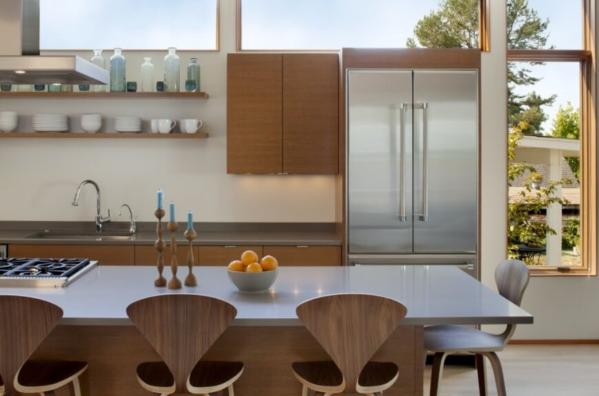 Sharp, natural wood textures abound on cupboards, island body, and seating in this kitchen, contrasting with white walls and metallic countertops. Matching wood shelving is built into wall above sink area, with array of windows above providing natural light.