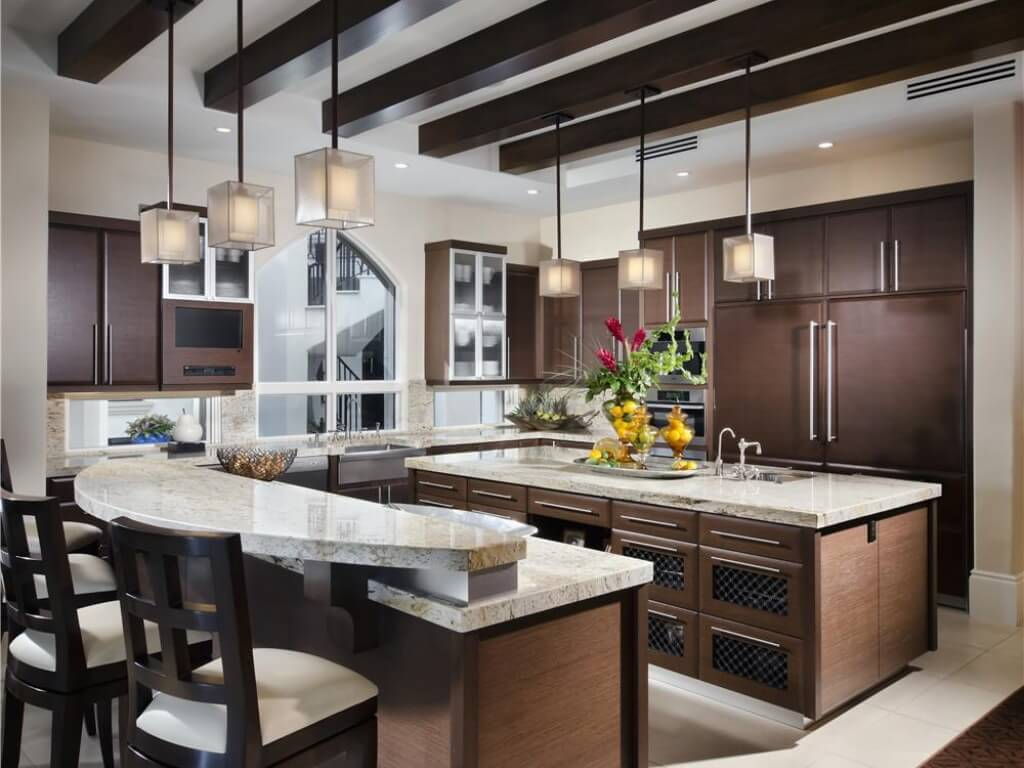 High contrast kitchen places dark natural wood textures between light marble countertops and flooring. Large island featuring sink stands with two-tier island beneath cubic chandeliers and dark wood exposed beams.