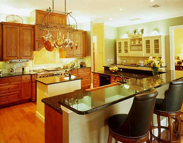 Another kitchen packing a large amount of variety and detail: dark marble countertops stand over natural wood cabinetry, with white island at center. Wraparound L-shaped island features dining space on raised tier.