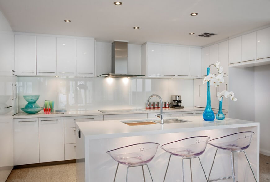 Bright, glossy white surfaces about on the cupboards, backsplash, and island in this modern kitchen. Island features space for dining and full sink, while beige tile flooring contrasts with bright tones well.