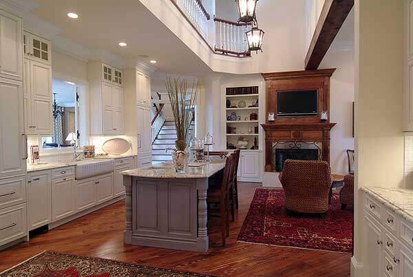 Two story kitchen space is overlooked by catwalk, with lush dark hardwood flooring, dark brown island with marble countertop, and surrounded with floor to ceiling white cabinetry.