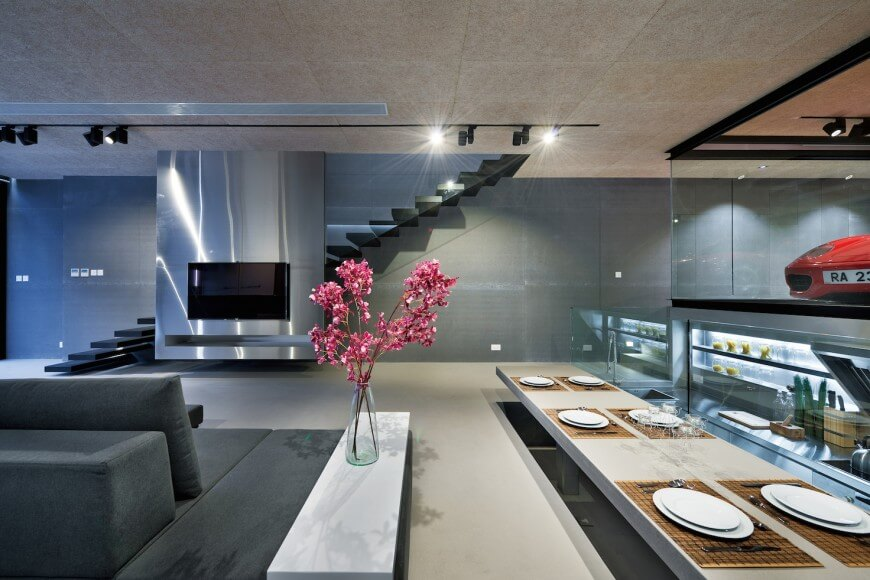 An open dining room with lowered dining table. Kitchen and living room areas off to the right and left. Glass-shrouded stairs behind a metallic media slab.