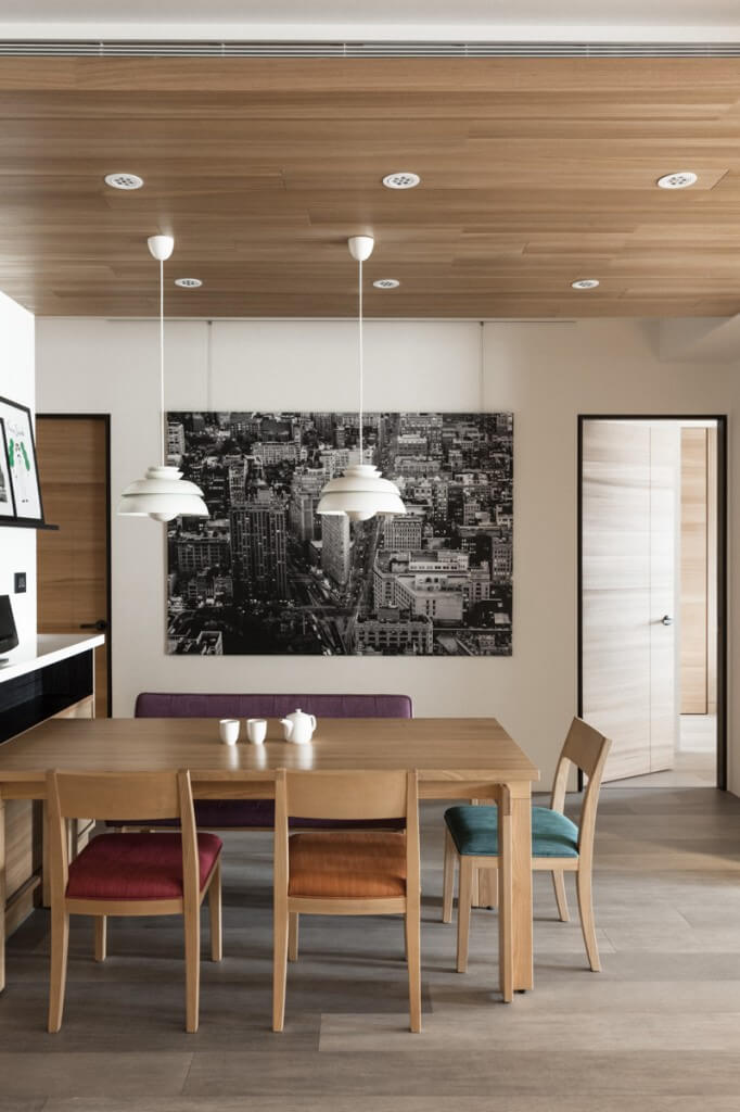 Simple dining area with three chairs and a bench. Cushions in variable colors brighten the space. A cityscape hangs on the wall behind.