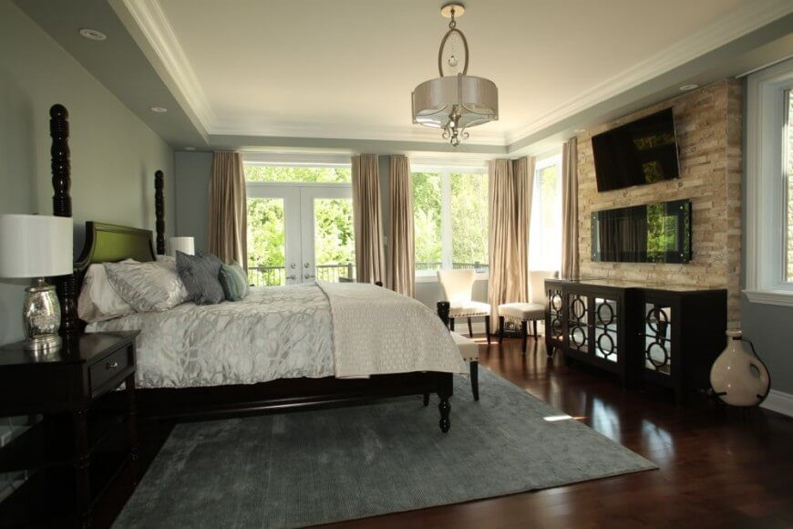 This stunning bedroom features a cherry-tone hardwood flooring that complements the darker furniture nicely. A chandelier observes the room below it, while plenty of natural light is allowed to flood through the windows.  A wall mounted TV can be seen high on the wall above the inset fireplace and unique mirrored chest of drawers.