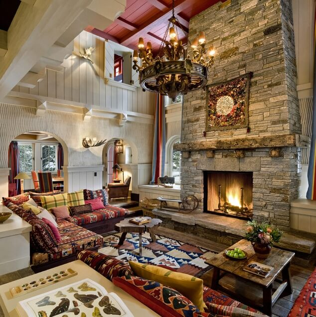 This Eclectic living room features a large stone fireplace and plenty of pace on the couch for relaxing. A rustic mantle sits just above the fire, and a colorful decorative textile hangs above the mantle. The wavy lines on the adjacent wall create an interesting effect, while the antler wall lamp accents the space.