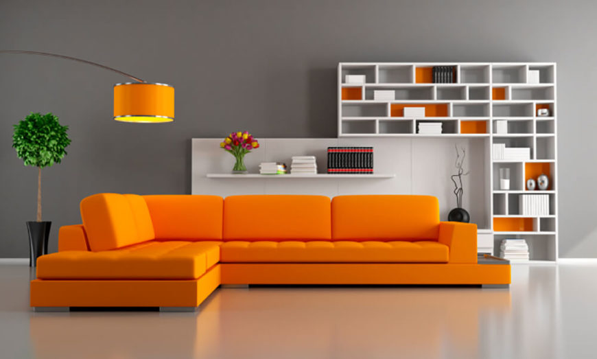 The bright orange couch is impossible to ignore in this living room space. A hanging lamp matches the vibrant couch, with small sections of the shelving unit behind the couch also matching the orange. With such a unique color scheme, this living room does not need too many decorations, the colors accent the space well enough on their own.
