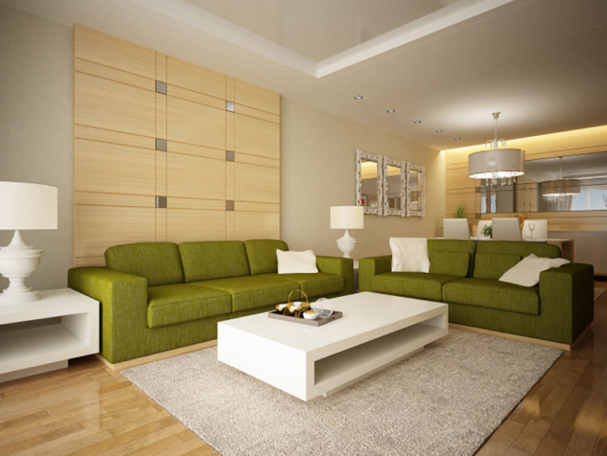 This living room is bright and spacious, with a comfortable pair of green couches, and a large square rug. The walls feature a set of wooden panels with small squares of tile as accents. Beyond the living room, you can see a dining table, complete with mirrors hanging on the adjacent wall.