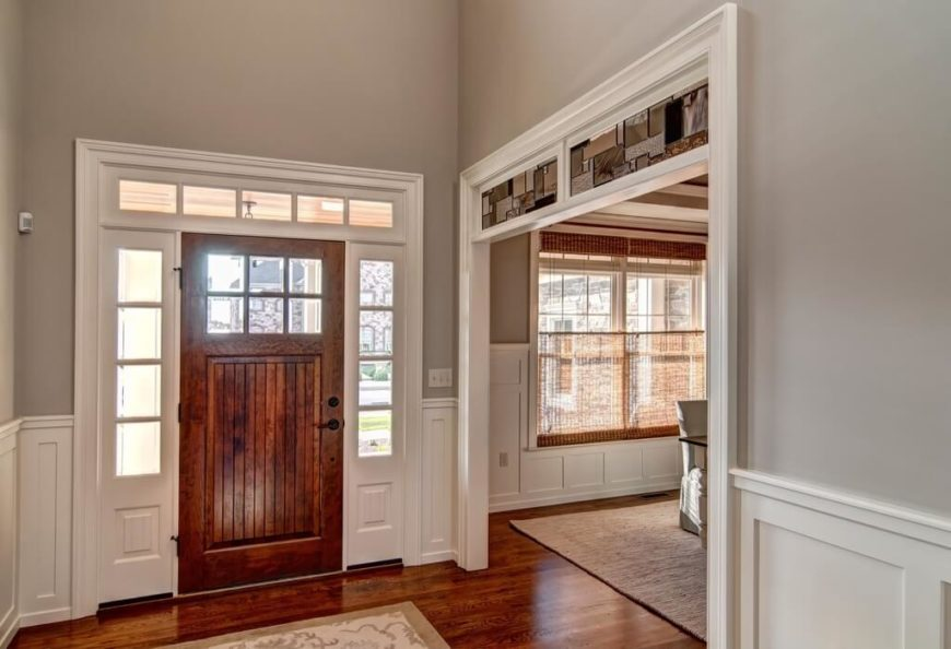 Classic and simple, this design allows for the bold wood floors to stand out against the neutral colors of the rest of the room. Large windows let in plenty of light to highlight the red hue of the floors. The detail of the multi-textured stained glass above the archway into the dining room is a great touch.