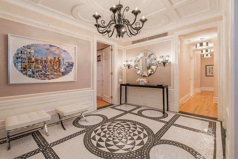 The patterns of the mosaic floor mimics the pattern of the ceiling. The round shapes are carried through the room in the mirror and the shape of the wall art. You can also see it down the hallway in the pendant lights hung there. Accents of black are found in the chandelier, side table, and the floor tiles.