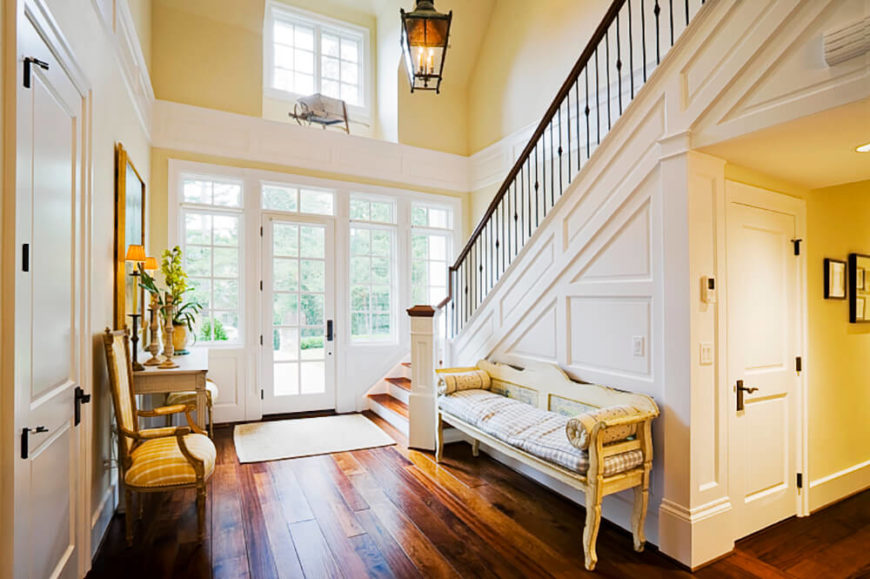 Butter yellow walls highlight the golden tones in the wood floor and add golden color to the space in the reflected light. Crisp white wainscoting helps to reflect that golden color further into the room while subtle accents of black brings added interest to the room.