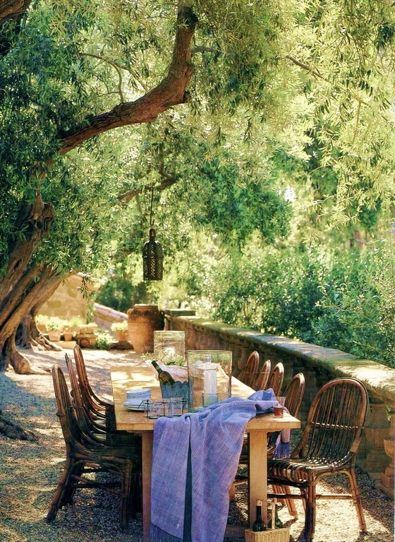 Under this shady tree sits a long table with plenty of seating. The setup here is reminiscent of something from a storybook. With the right table you can turn your backyard into its own storybook getaway.