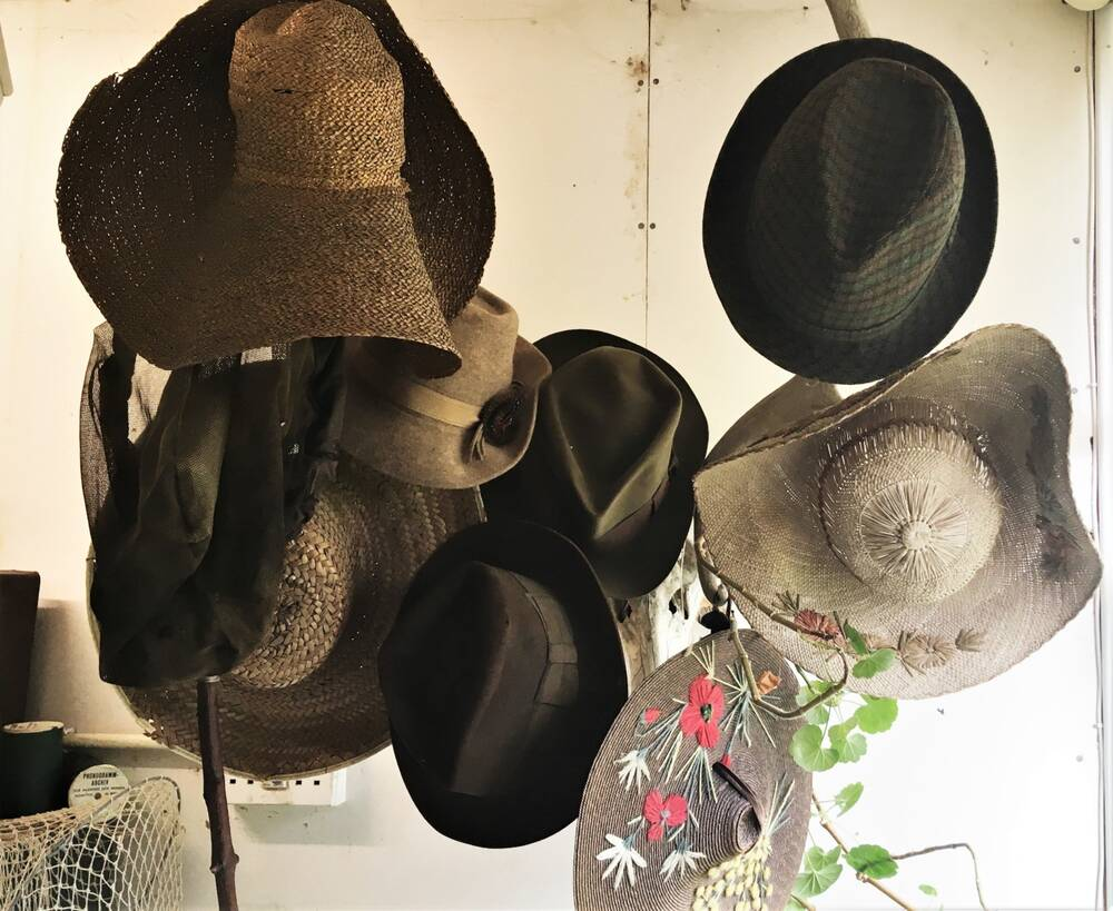 A group of hats are displayed on a hatstand. Most are brown felt but a couple are decorated with flowers and leaves.