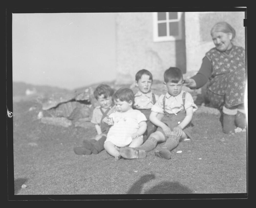 A black and white photograph of four very young children sitting together on some grass outside a croft house. An older woman sits just behind them, touching the ear of the closest boy. The shadow of the photographer can be seen on the lawn, with an arm raised in the air.