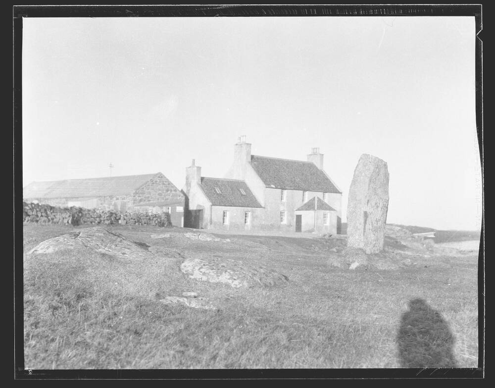 A black and white photograph of a white stone building with a tiled roof. A large stone outbuilding stands to the left. In front of the inn is a very large single standing stone. The shadow of the photographer lies on the grass in front of the stone.