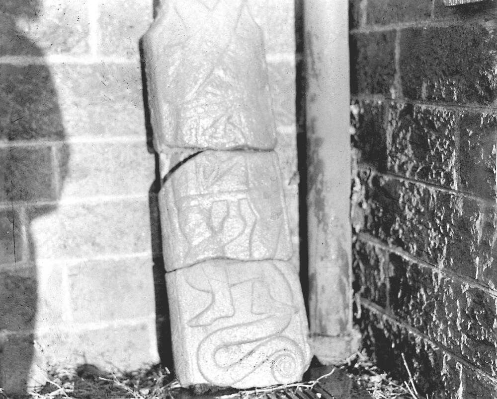 A black and white photograph of a large slab with heraldic-type carvings upon it. It leans against a brick wall beside a drainpipe. The photographer's shadow runs up the wall beside the slab.