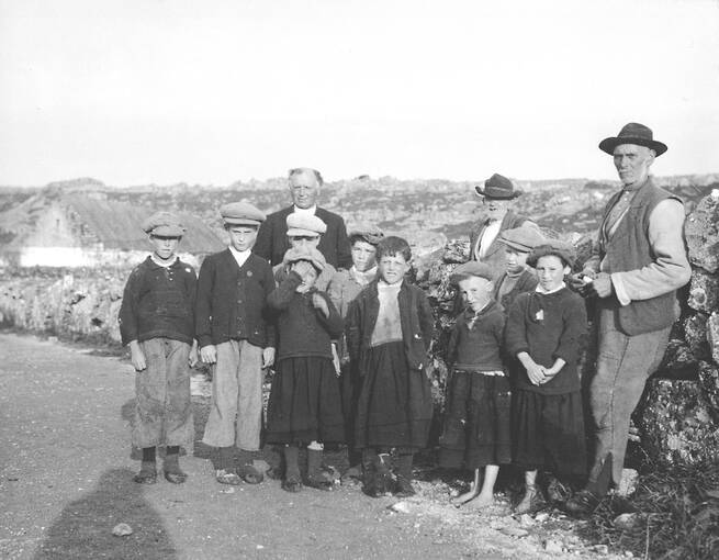 A black and white photograph of a group of young boys, with three older men standing behind them. They stand on a stone road, with some croft houses in the background. Some of the boys are barefoot. Most are scrunching up their faces, or shielding their eyes, against the sun. The shadow of the photographer falls to the left of the photo.