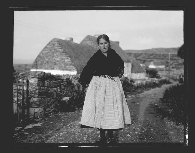A black and white photograph of a woman walking along a stone road past croft houses. She wears a dark woollen shawl around her shoulders and has a paler skirt. The long shadow of the photographer falls along the road on the right.