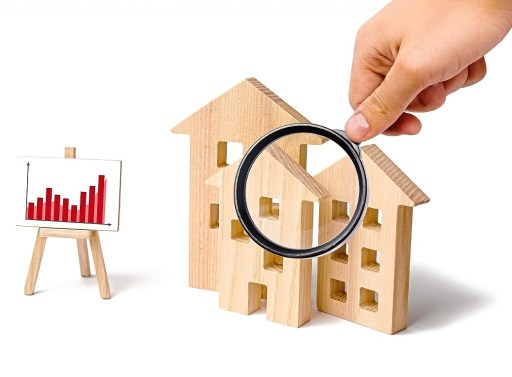 Magnifying glass is looking at the wooden houses with a stand of graphics and information. Growing demand for housing and real estate. Statistics on the state of the market. Investments.