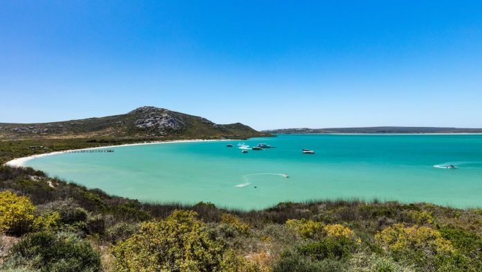 A scenic view of the turquoise water of Langebaan lagoon at Kraalbaai with houseboats and other boats in the water with a clear blue sky