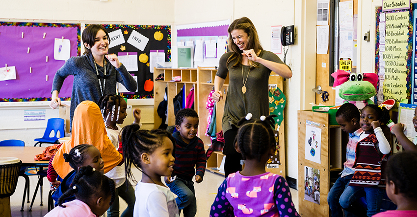 Teacher and Teaching Artist dancing with children in the classroom