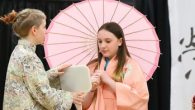 Students in Asian costumes with umbrella