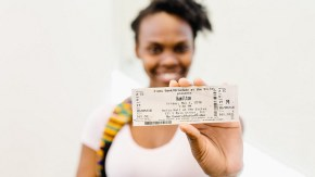 young woman holding a Hamilton ticket