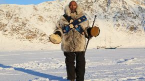 man with tambourine in front of a snow covered mountain
