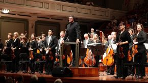 conductor and symphony standing on stage with instruments