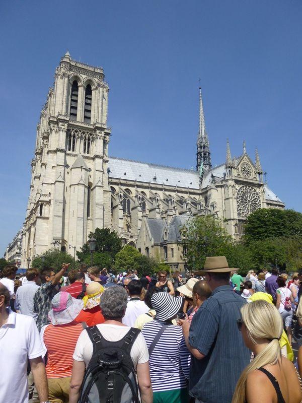 Imagine din arhivă cu turiști așteptând la coadă pentru a intra în Catedrala Notre Dame, Paris.