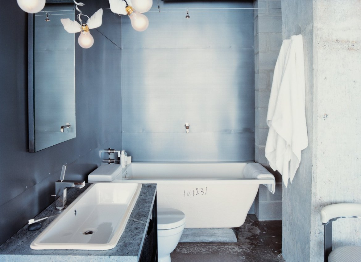 Winged light bulbs, part of an Ingo Maurer fixture, bring levity to this bathroom. The space features a zinc wall by Houston metalworker George Sacaris, who also did the bathroom and kitchen cabinets.