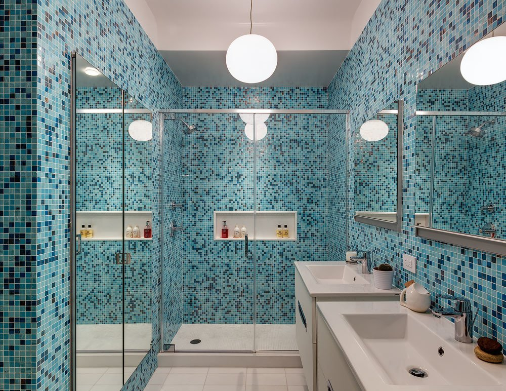 Bold color is embraced in the home's first bathroom, with tilework by Trend Mosiacs. Faucets are by Grohe and vanities are by Hastings. A Flos Glo-Ball pendant light illuminates the space.