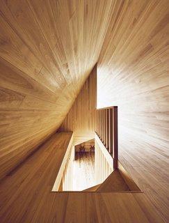 """En regardant vers le bas l'escalier d'en haut révèle une autre vue de la forme """"A"""" de l'étage supérieur avec des angles contrastés créés par la lumière et l'ombre."""