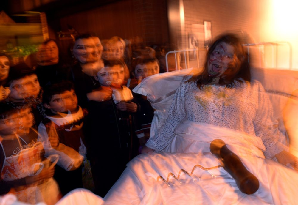 "A woman dressed up as a character from the movie ""The Exorcist"" reacts during Halloween in La Fresneda"
