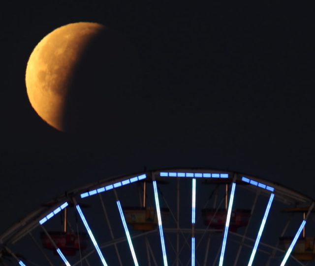A Lunar Eclipse Of A Full Blue Moon Is Seen Above The Ferris Wheel