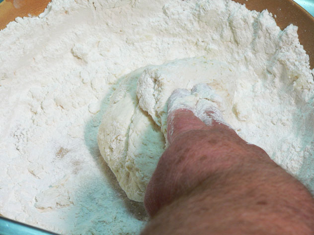 Fold the dough over on top of itself a time or two as you gently knead it into a smoother package. You're still working a little more flour into it to take away some of the tackiness of the dough. You will want it slightly tacky but not wet. Turn the dough ball over, sprinkle a little more flour on top, and knead it a time or two more. This will take about 30 to 35 seconds, so don't over work it.