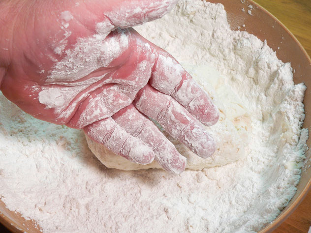With the sticky dough off your fingers, get some more clean flour and dust both hands a bit.