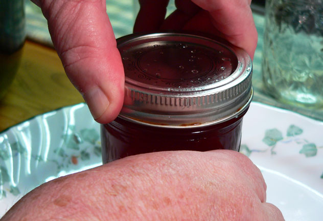 """The lid lifter tool is also used to remove one of the bands from the water. Carefully apply the band and screw it down, making sure it's going on properly. With the band on the jar, tighten the band """"finger tight."""" This means you're just snugging the band to the jar without exerting any extra pressure to tighten it down on top."""