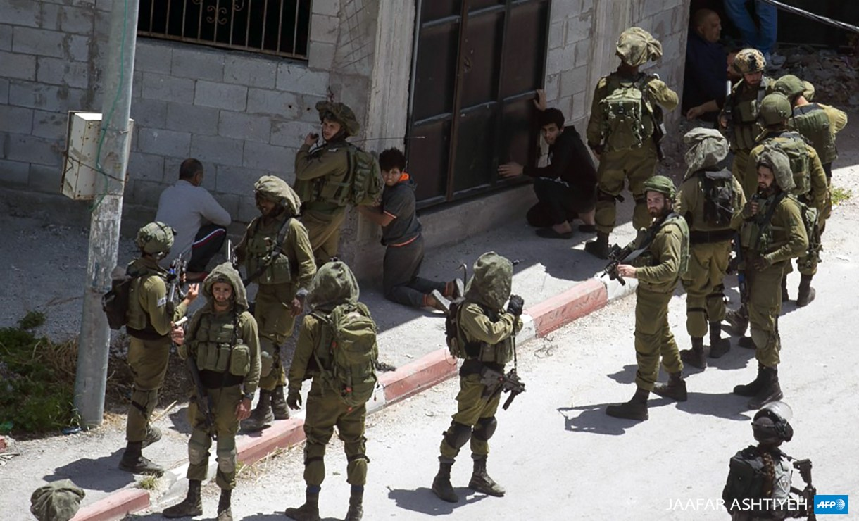 Israeli forces detain 13-year-old Khaled Abu Baker (kneeling center) in the occupied West Bank town of Yabad on May 12, 2020.(Photo: Jaafar Ashtiyeh / AFP)
