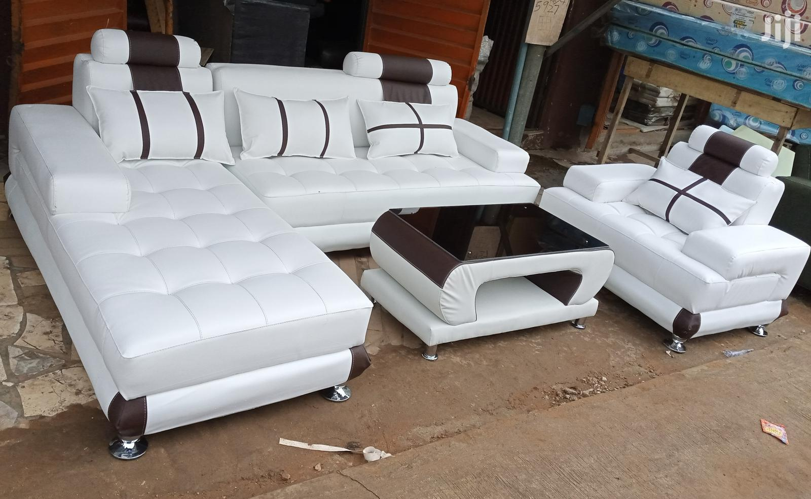 l shaped sofa with single seater chair and a centre table white couch
