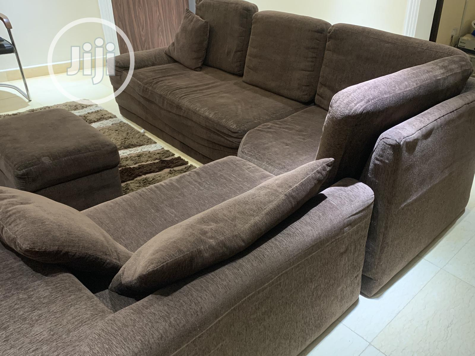 brown l shaped fabric sofa with ottoman and centre rug