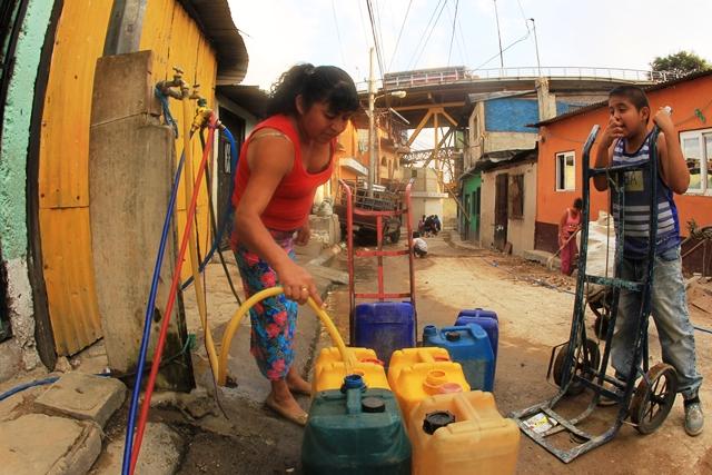 La única calle ancha del barrio se pinta de colores cuando los vecinos del sector 4 desfilan en las calles con sus recipientes para abastecerse de agua, ya que tenerla en casa es una labor titánica en el lugar, que solo cuenta con dos chorros públicos. (Foto Prensa Libre: Esbin García)