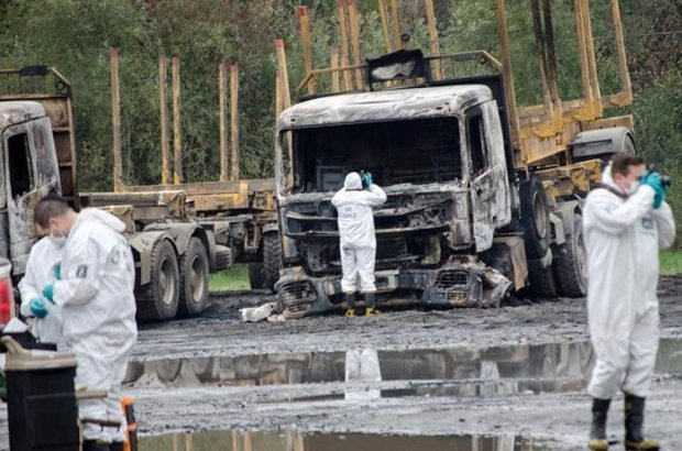 Policías inspeccionan el lugar donde fueron quemados 29 camiones. (EFE).