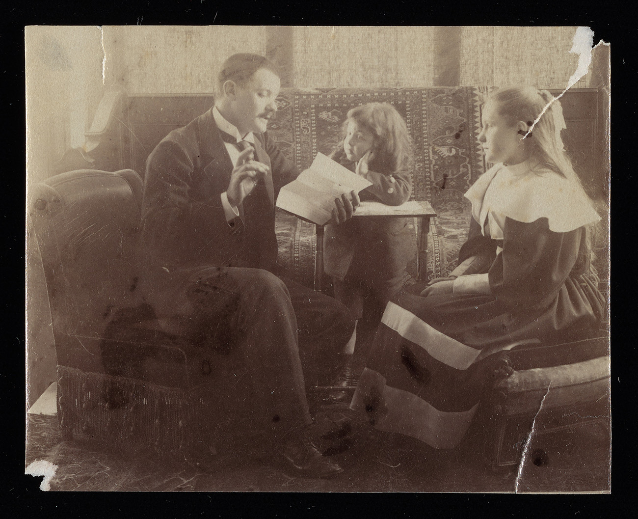Man reading to his two daughters. The print is aged, bent and torn in a few locations.