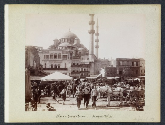 Bustling marketplace with a large Mosque in the background.